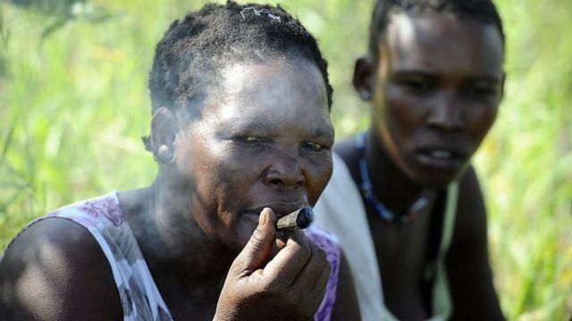 Une femme bushman fumant une cigarette.