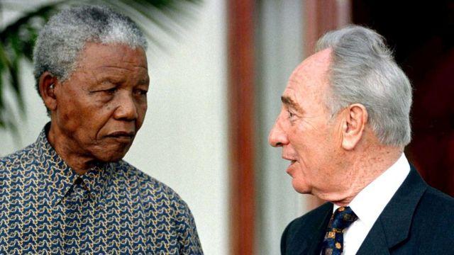 साल 1996 में दक्षिण अफ़्रीका के केपटाउन में राष्ट्रपति नेलशन मंडेला से मिलते शिमोन पेरेज़.