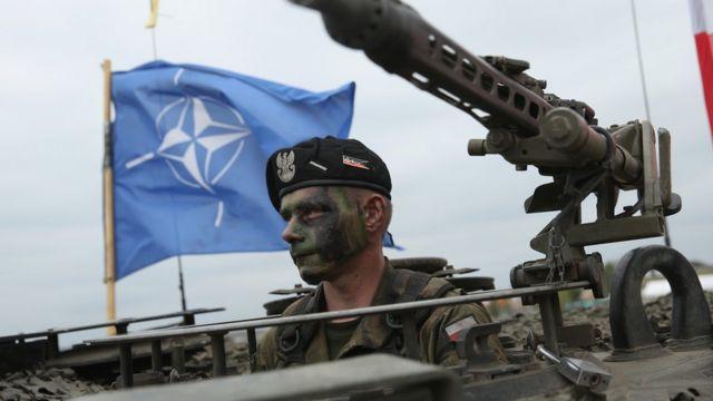 Polşalı əsgər NATO bayrağının önündə