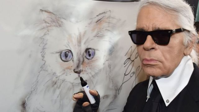 Lagerfeld posing with a painting of his cat