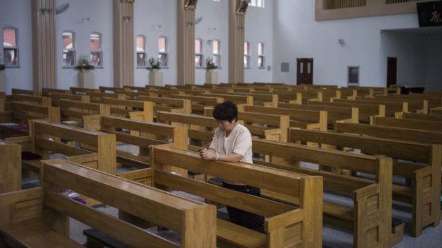 A woman prays alone in a Catholic church in Tianjin. Many Christians in China are part of 'underground' congregations who maintain their independence from state-run churches