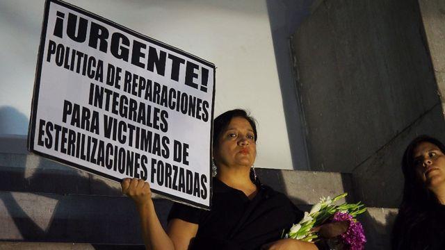 Una mujer sostiene un cartel durante una protesta exigiendo compensación en 2017