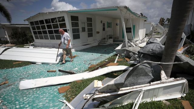 شخص يتفقد آثار الإعصار أمام منزله في فلوريدا