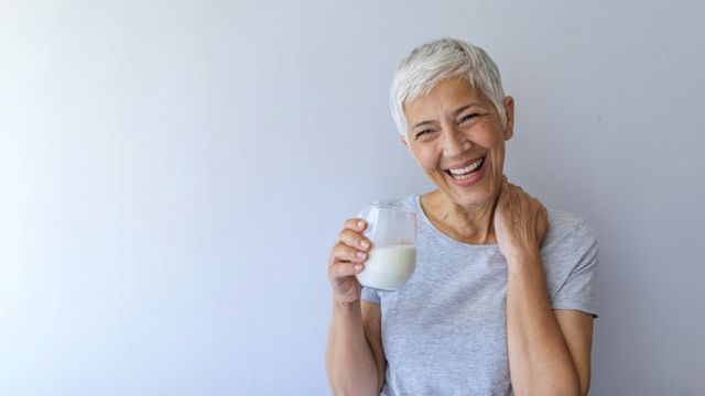 Женщина со стаканом белой жидкости