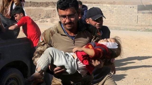 मोसुल के तहरीर ज़िले में एक घायल बच्ची को ले जाते इराक़ी सैनिक.