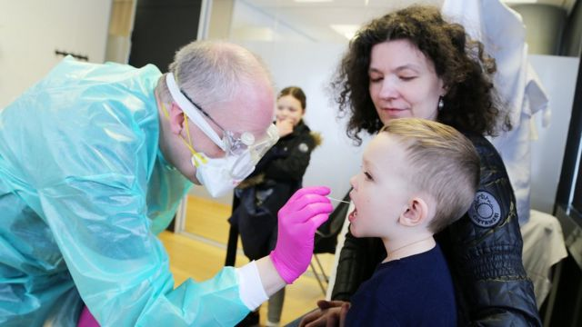 Profissional de saúde com equipamento de proteção recolhe amostra de boca de criança, com a mão ao lado