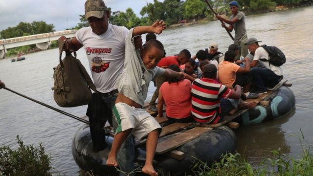 Una balsa repleta de migrantes cruza el río que funciona como un límite natural entre Guatemala y México.