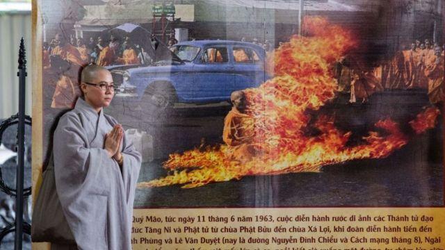 Một tu sĩ Phật giáo đứng cạnh một biểu ngữ với hình ảnh nhà sư Thích Quảng Đức, người đã tự thiêu trên một góc phố sầm uất Sài Gòn năm 1963, tại chùa Việt Nam Quốc Tự ở thành phố Hồ Chí Minh vào tháng 6/2018.