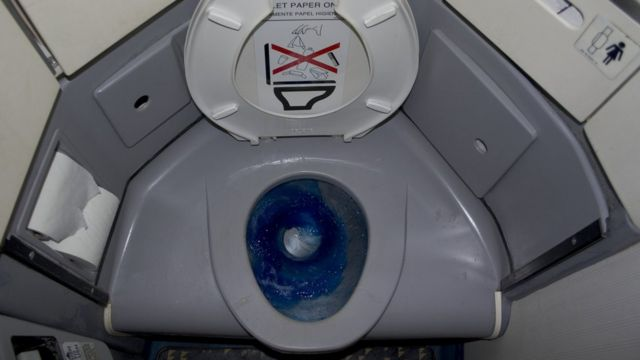 An aeroplane toilet showing blue disinfectant