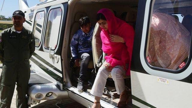 Malala desce do helicóptero com sua família