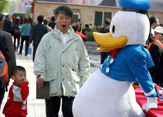 Un empleado de una agencia de turismo de China vestido del pato Donald en Pekín.