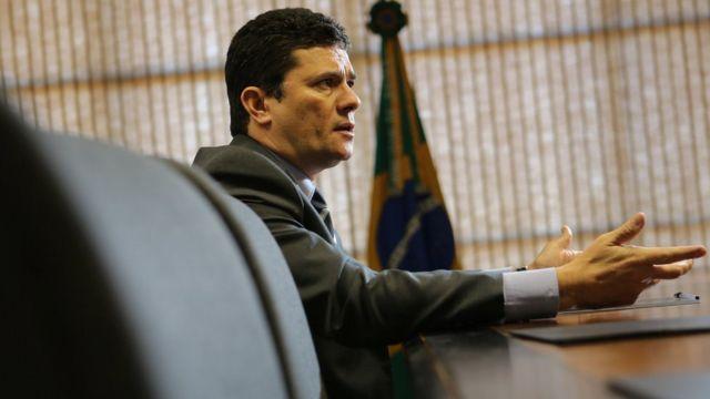 Sergio Moro aparece de perfil falando dentro do escritório