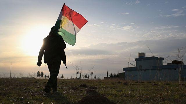 Figura caminando a contraluz con una bandera del Kurdistán iraquí