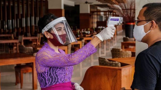 Una mujer en un restaurante de Bali, Indonesia, toma la temperatura de una cliente