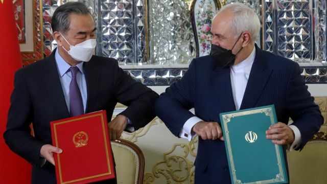 """Iran""""s Foreign Minister Mohammad Javad Zarif and China""""s Foreign Minister Wang Yi bump elbows during the signing ceremony of a 25-year cooperation agreement, in Tehran, Iran March 27, 2021."""