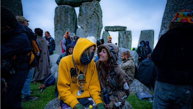 People inside the stone-circle during Summer Solstice at Stonehenge, where some people jumped over the fence to enter the site to watch the sun rise at dawn of the longest day in the UK. The stones have been officially closed for the celebrations, which see huge crowds inside the circle, due to the coronavirus lockdown extension.