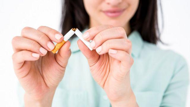 Mujer partiendo cigarrillo.