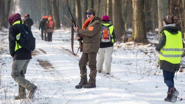 Lovac sa puškom gleda okolo dok aktivsti za prava životinja obučeni u vidljive žute prsluke šetaju okružujući ga sa svih strana