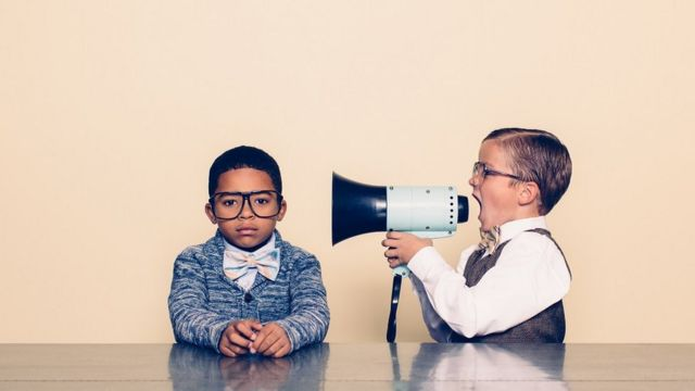 A young boy talking through a megaphone into the ear of another boy who is not listening and ignoring him. The boys are dressed in bowties and glasses / Retro styling.