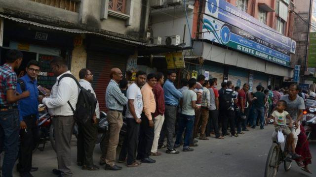 असम के सिलिगुड़ी में पैसे के लिए एटीएम के बाहर खड़े लोग.