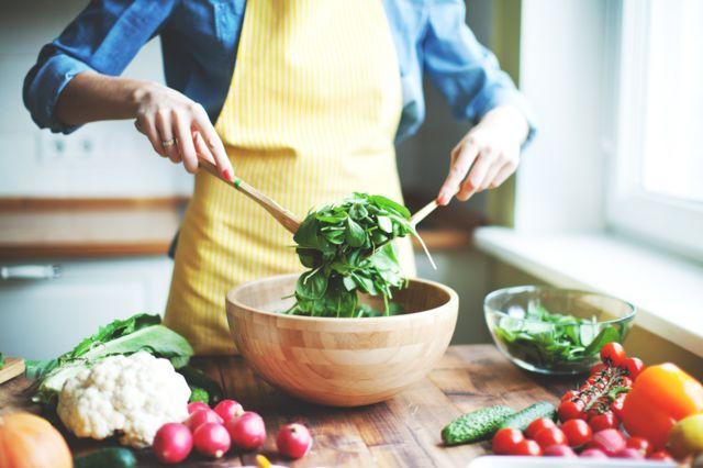 Женщина готовит овощной салат