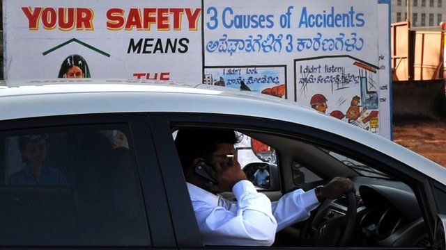 An Indian man talks on his mobile phone as he drives past a traffic awareness poster on a busy road in Bangalore