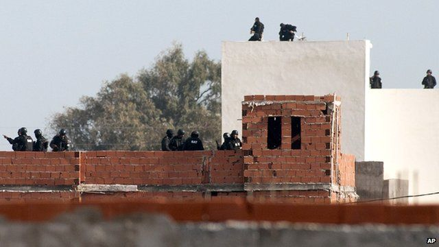 Units from the Tunisian National Guard prepare to storm a house containing militants in Tunis