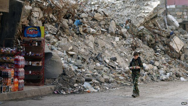 Boy walks past destroyed building in Deir Ez-Zor