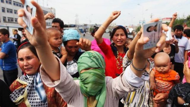 An Uighur woman holds her relatives' ID cards who are are currently detained, as she and others protests on a street on 7 July 2009 in Urumqi, the capital of Xinjiang