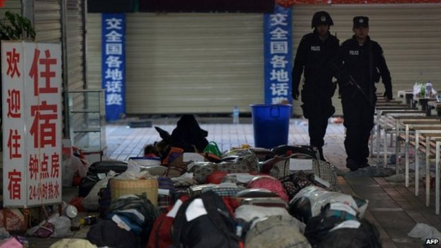 Chinese police walk past abandoned luggage at the scene of an attack at the main train station in Kunming, Yunnan province on 2 March 2014