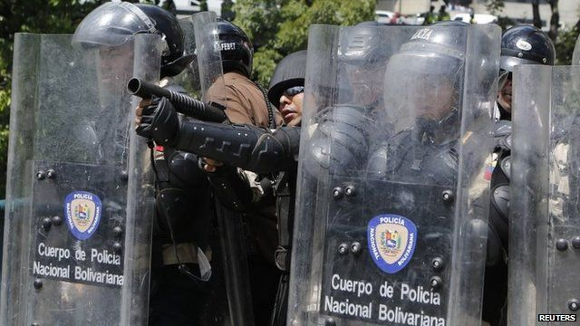 A riot police officer prepares to fire teargas at anti-government protesters in Caracas, on March 20, 2014.