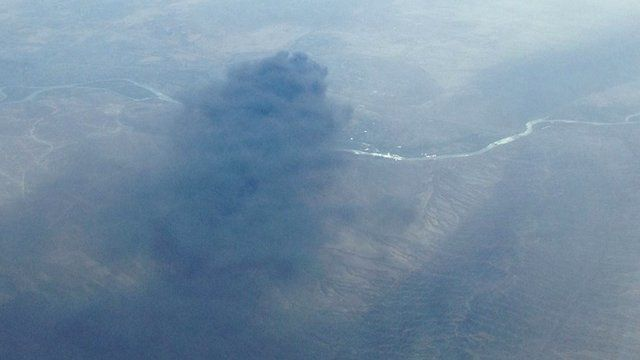 Plumes of smoke from burning Baji oil refinery
