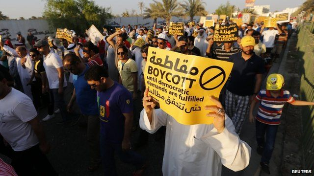 Protesters hold signs as they march during a rally organised by Bahrain's main opposition party Al Wefaq in Budaiya, west of Manama