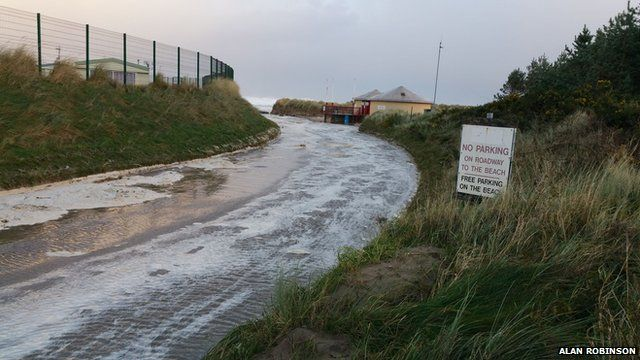 The tide has flooded the road beside Benone beach near Limavady