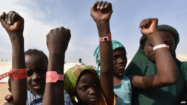 Nigerian refugee children show their UNHCR wristband in a United Nations Refugee Agency refugee camp in Baga Sola by Lake Chad