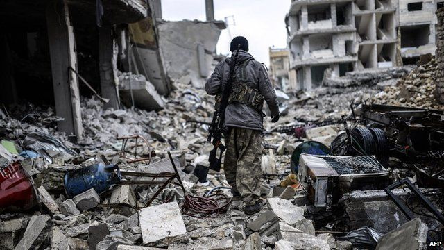 A Kurdish marksman, walks in the rubble of the Syrian town of Kobane on 30 January, 2015