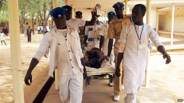 Health workers carry an injured victim of a suicide blast in the northeast Nigerian town of Potiskum on 24 February 2015