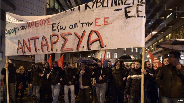 """People carry banner reading """"out of EU"""" and """"cancel the debt"""" during a demonstration in Athens on 26 February 26"""