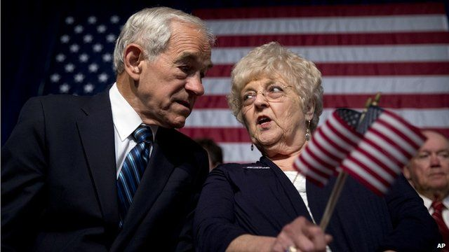 Former Texas Rep Ron Paul and his wife, Carol, talk in front of an American flag
