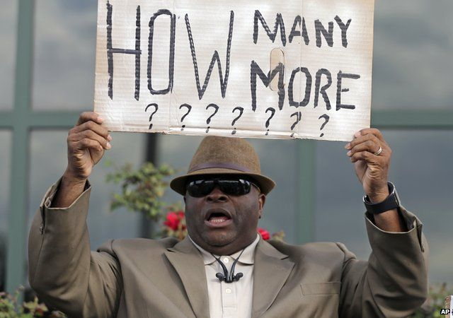"""Man holding a sign that asks """"How many more?"""""""