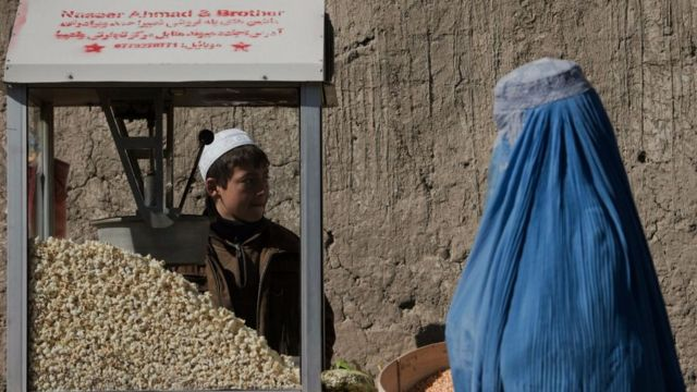 Un niño vende palomitas de maíz en Afganistán