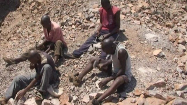Men in the search for diamonds using hammers on rocks.