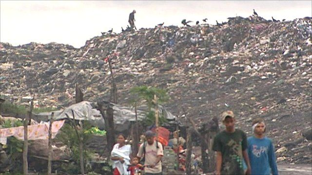 People walking away from La Churega open-air dump