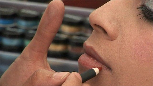 A woman has make-up applied