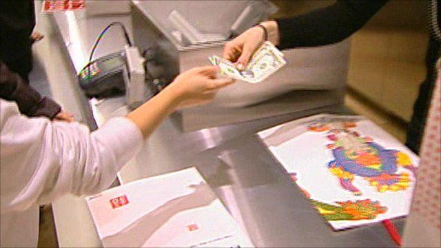 A shopper hands over money at a department store.