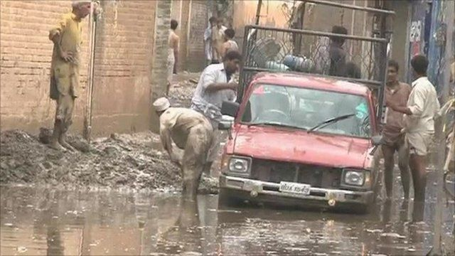 Men digging car out of flooded muddy street