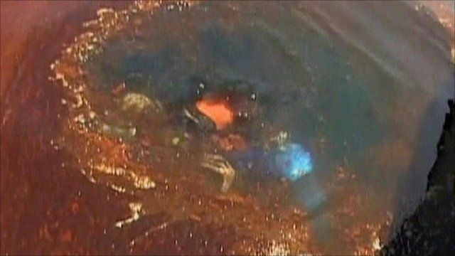 Diver seen through hole in slick of oil