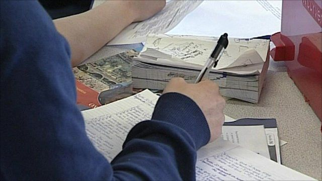 pupil writing in book