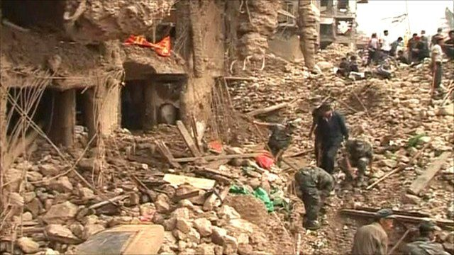 Rescue workers search through rubble