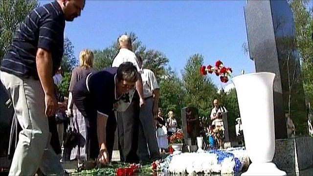 Russians lay flowers on a grave